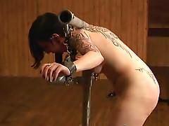 Iron bondage keeps tattooed slut in place