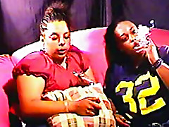 Two ebony and hot chicks are smoking cigarettes