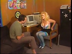 Busty older blond in thigh-highs kneels to engulf younger dude's cock