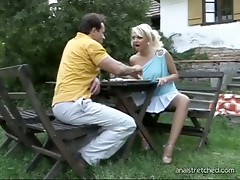 A blond gal and a guy are eating at a picinic table. The gal lowers her dress and shows her tits, then this babe rubs her pussy. Next, the both of them are on the ground, fucking doggy style. In betwixt poses this babe gives him blow jobs.