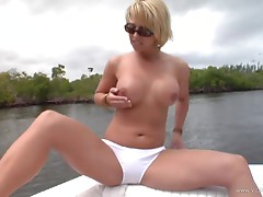 Erotic solo model with tattoo fondling her fake tits before fingering her pussy on a yacht outdoor