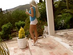 Long-haired blonde babe toys her ass in the courtyard
